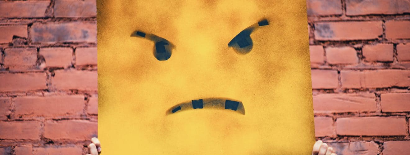 Angry face painted on yellow board